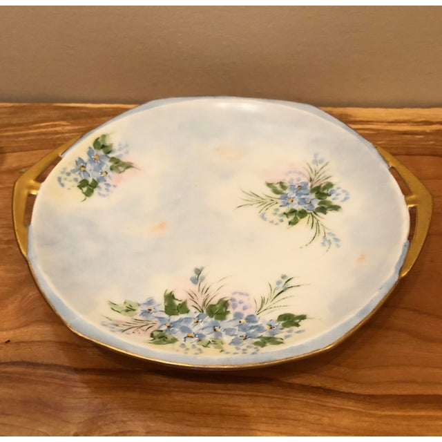 Sweet blue posies and gilded handles make this a charming addition to any antique decor. Mark on the bottom is blurry but...
