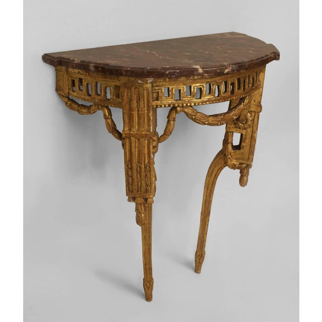 Pair of late 18th century Italian neoclassical marble and giltwood bracket console tables with shaped demilune rouge...