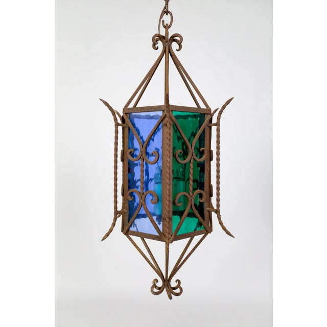 A striking, 1920's, rust iron and mixed metal, Gothic Revival lantern decked with scrolls and twisted spears; a hexagon...