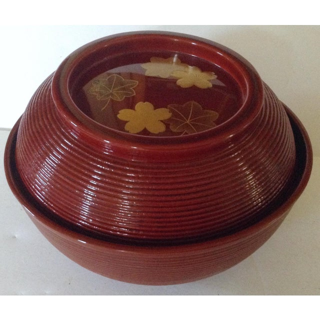 This Japanese lacquered soup bowl looks modest with the lid in place. There is only a hint of the surprise inside by the...