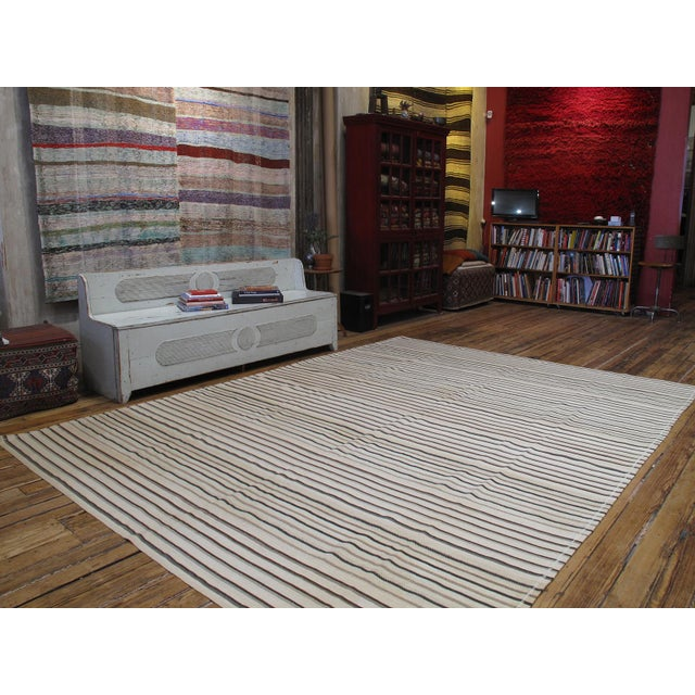 A large tribal flat-weave from Central Turkey with alternating stripes of brown and black on an ivory ground - all...