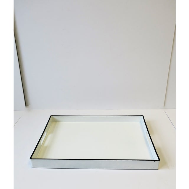 A great Modern or Minimalist style white and black lacquer rectangular serving tray with cut-out handles. Tray is white...