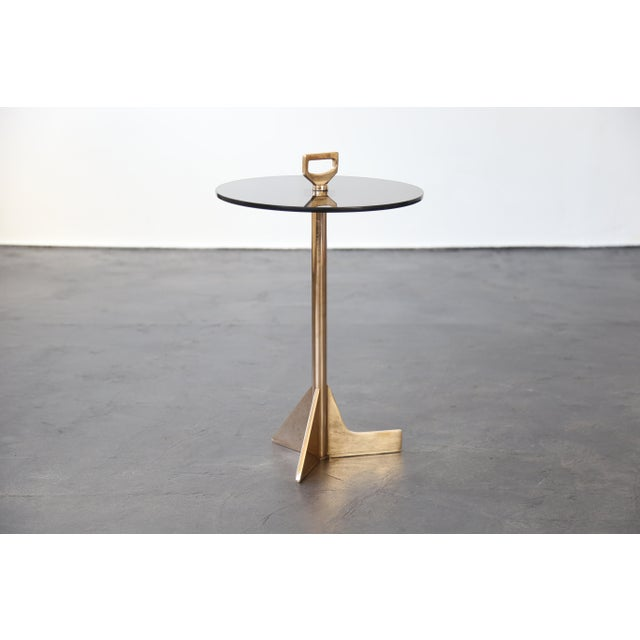 """This playful table made of cast bronze and smoked glass features asymmetrical """"feet"""" so that it might slide under a sofa..."""