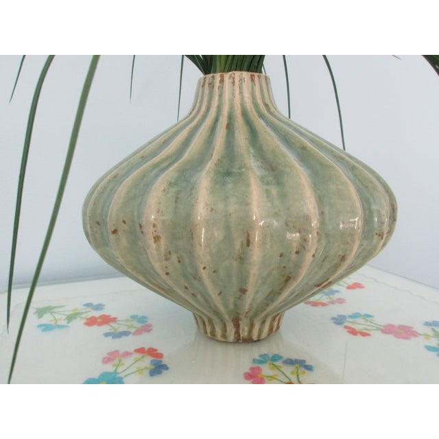 This Global Views teal colored cinched and fluted vase is beautiful work of art. We currently have faux grass reeds...