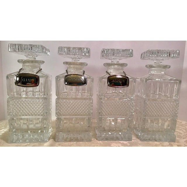Great mid-century English set of four crystal decanters with three silver plate tags - bourbon, gin, and scotch. Very...