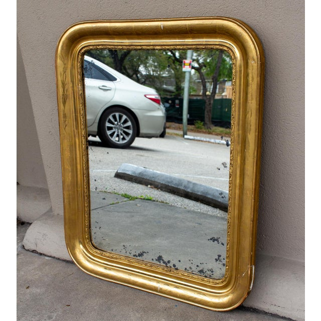 This antique French gilt mirror is a Louis Philippe style mirror with rounded corners. The bright gold gilt frame features...