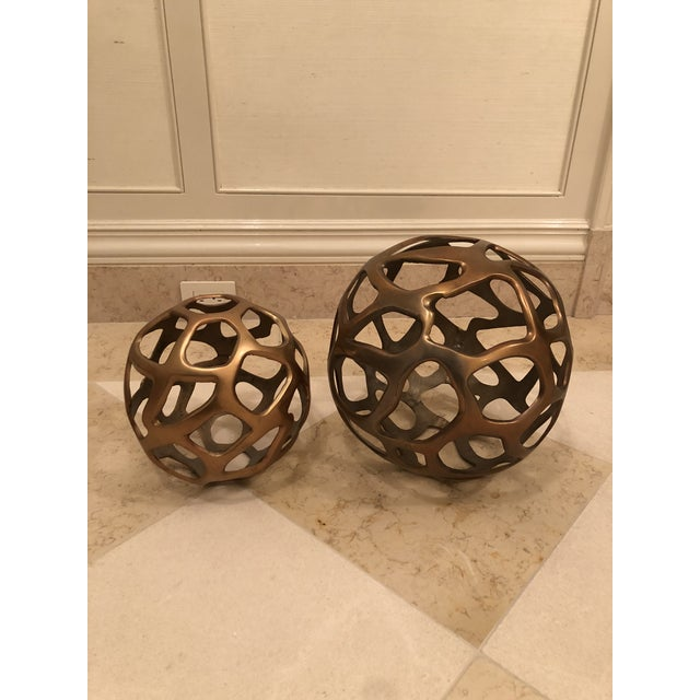 Create a modern statement with a set of two signature sphere sculpture swith asymmetrical honeycomb cut-outs. Set of 2...