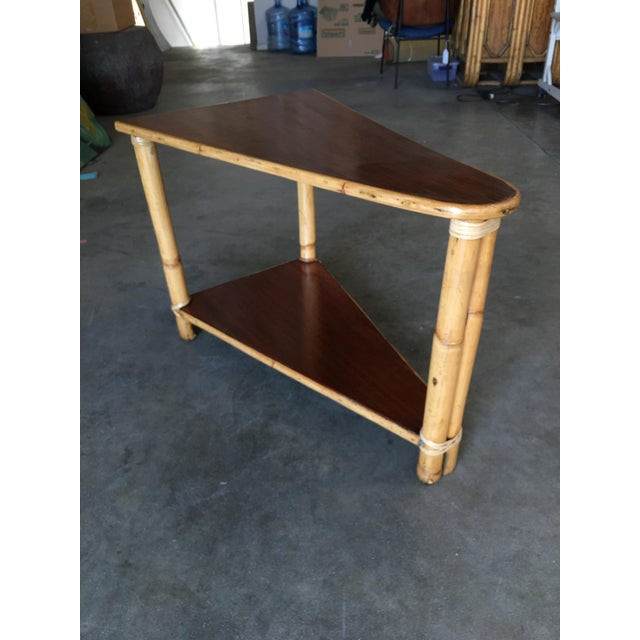 Vintage pole rattan leg two-tier triangle wedge table with two-tier mahogany tops. Great for use as a drinks table. All...