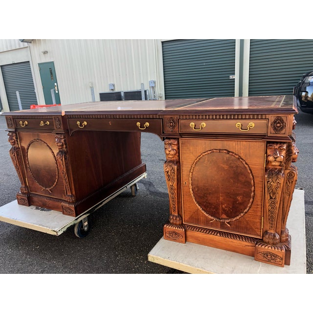 Stately mahogany Chippendale style double pedestal partners desk having burgundy tooled leather top, ornamental carved...