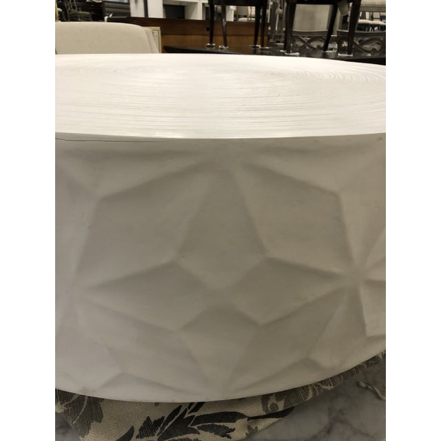 Create a focal point with this round cocktail table featuring a chalky white finish. The edge of the table is cat with a...