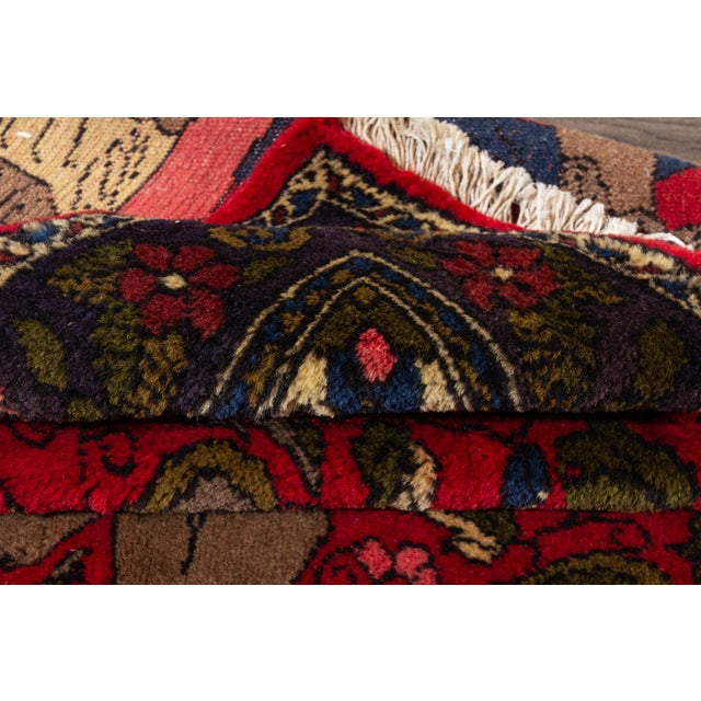 """A vintage hand-knotted Persian rug with a red pictorial motif. This rug measures at 2'2"""" x 3'4"""" Material: wool"""