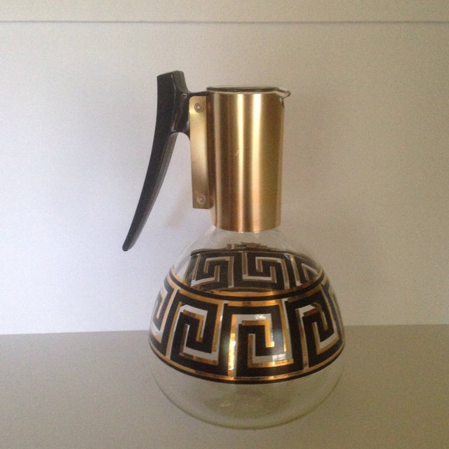 A Mid-Century style, glass coffee carafe. This vintage piece features a Greek key design in gold & black. Great addition...