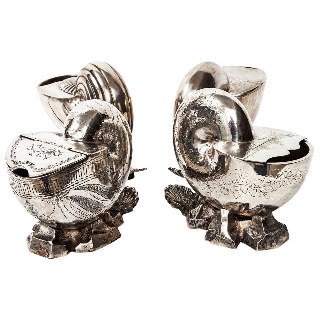 Four 19th century Victorian silver plate spoon warmers in the shape of nautilus shells resting on a bed of sea rocks...