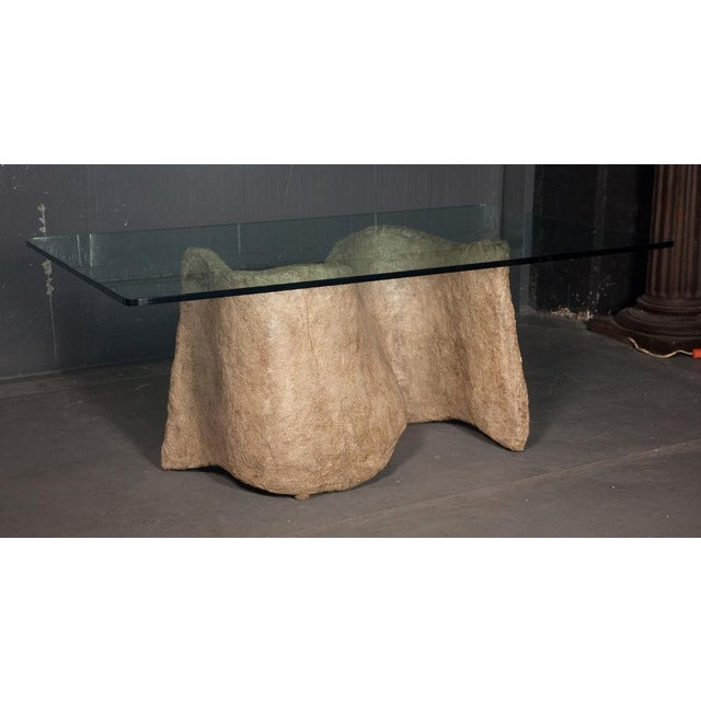A faux cast stone dining table in Seandel's Miro form, a serpentine shape with a thick glass top. This table was designed...