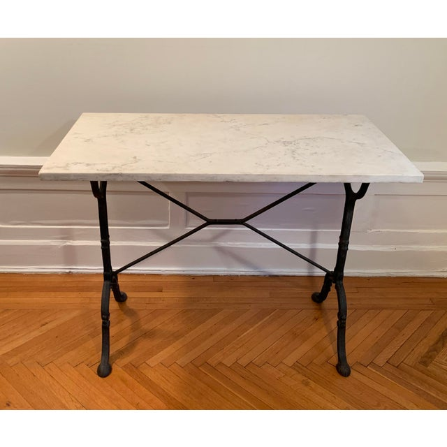 Marble top table with cast iron base in fair condition. Made in the mid 20th century.