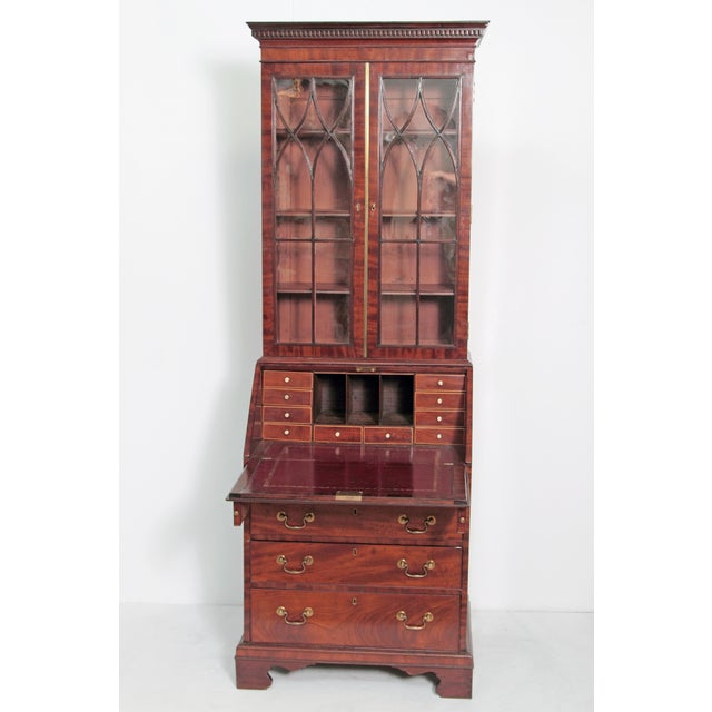 An 18th century George III period mahogany secretary bookcase, with glass paned doors above which open to reveal three (3)...
