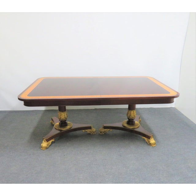 Baker Mahogany dining room table with carved and gilded double pedistals, satinwood and tulipwood banded veneer on top , 3...