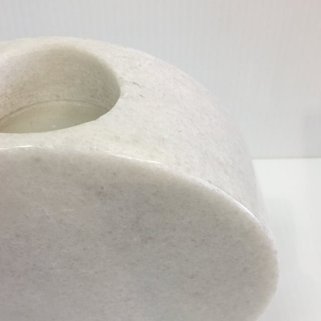 Almost round shape to hold a candle. Use alone or other items from the collection. Made of solid carved white marble.