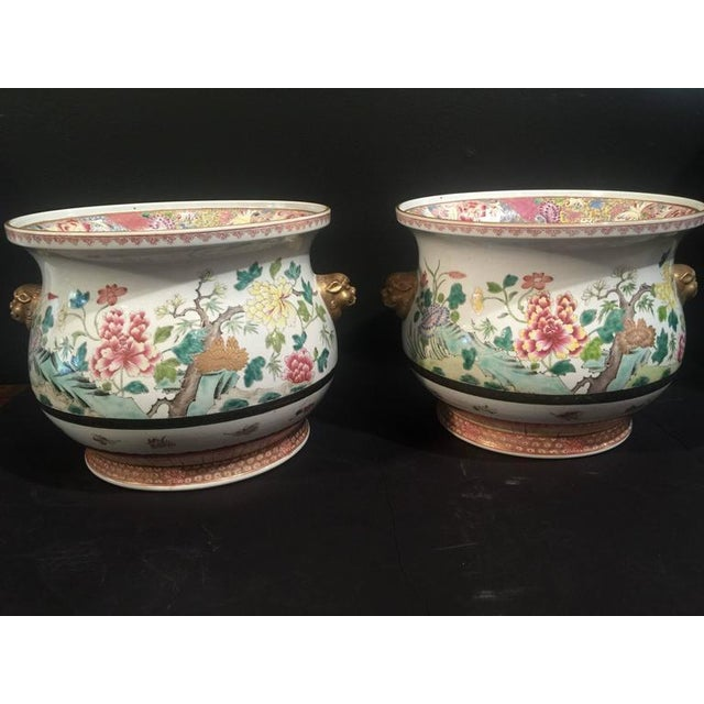 A stunning pair of Chinese porcelain cachepots, finely painted in famille rose enamels. The bulbous body features a...