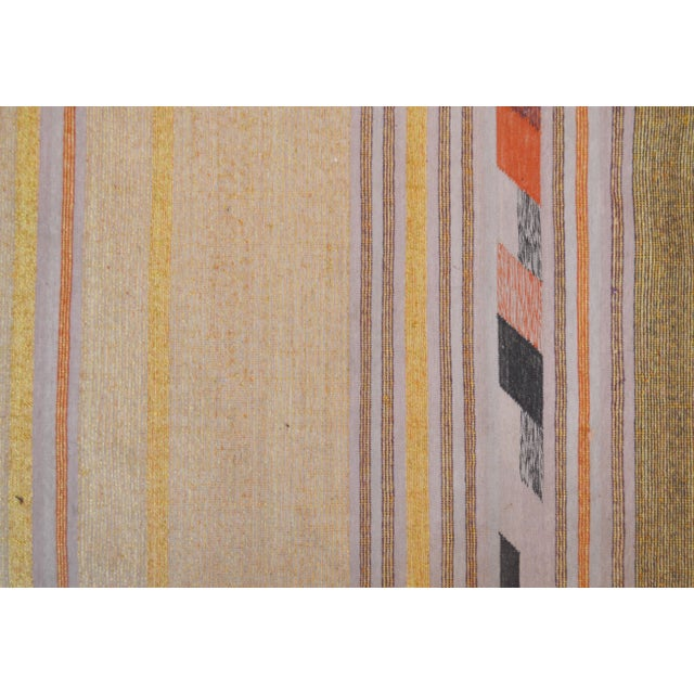 A beautiful hand woven rug made in India; an elegant lilac, pink and gold striped design with red tufts completes this...