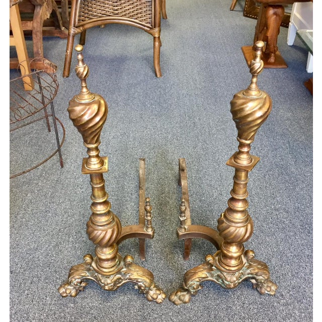 Sizable antique brass on copper twist feature andirons- a pair. These swivel on the base and are very sturdy.