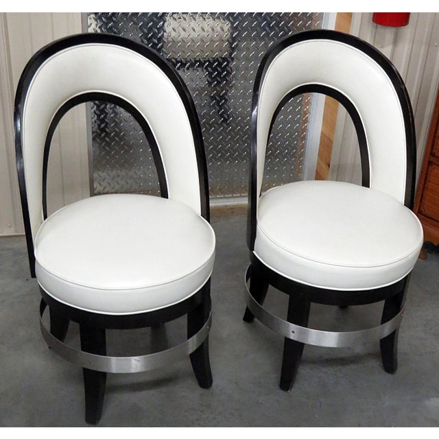 Pair of Mid-Century Modern swiveling club chairs with an ebonized frame and leather upholstery.
