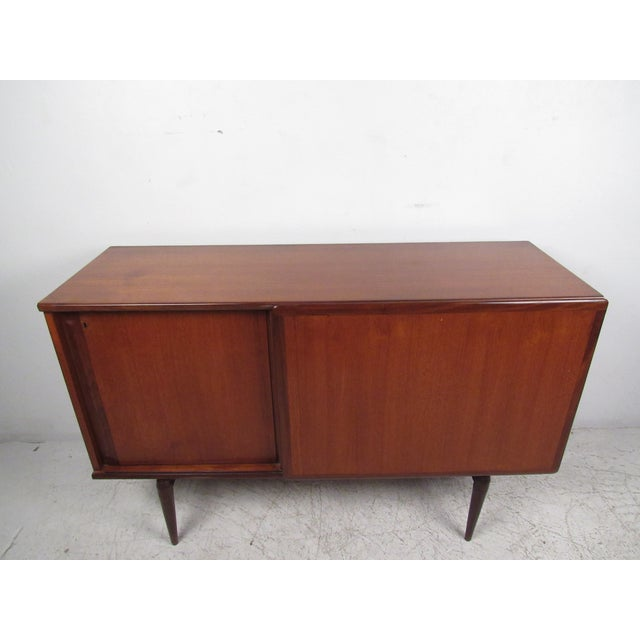 Unique mid-century modern sliding door cabinet with adjustable shelves and rich teak finish. A petite design with tapered...