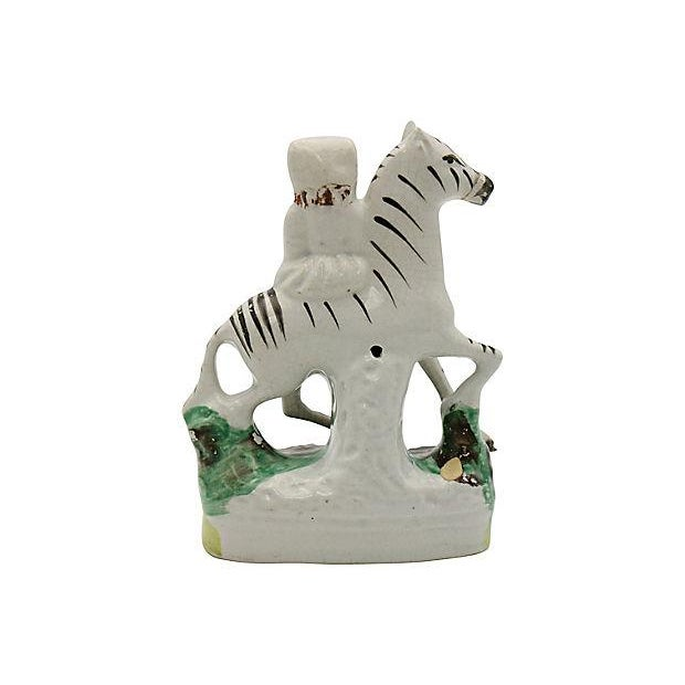 Antique English Staffordshire figure of a girl riding a zebra. As with most early Staffordshire, there is no maker's mark....