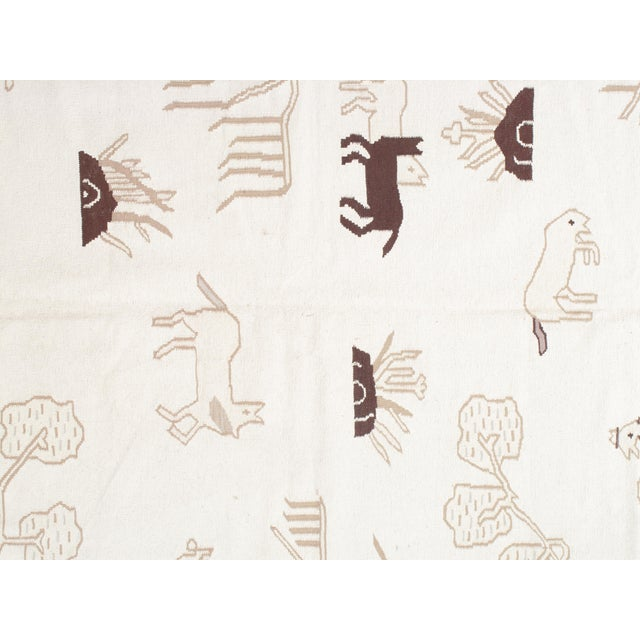 """Unusual design showing a range of animals on a clean white field, size: 6'2""""x9'"""
