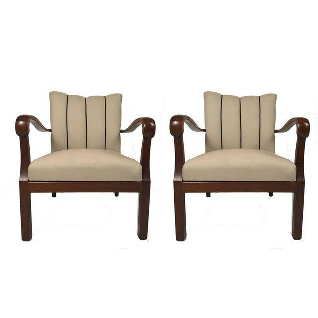 Elegant pair of Danish 1930s-1940s mahogany armchairs with exaggerated curved open arms. Newly upholstered in channeled...