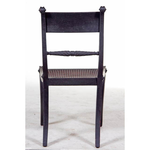 Classic pair of Regency period ebonized chairs on reeded saber legs with caned seats. We are offering a set of six later...