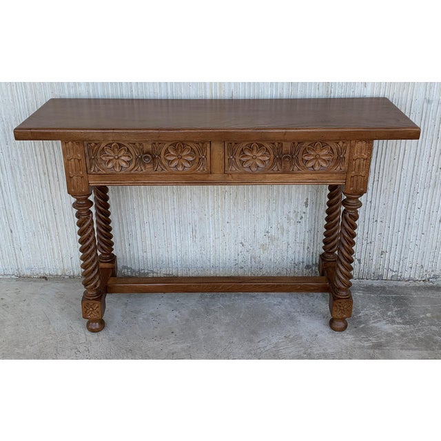 About Spanish Baroque carved walnut console table with two drawers, circa 1860. A 19th century walnut console table with a...
