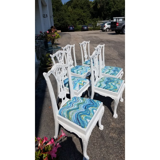 A set of six white painted Chippendale dining chairs with colorful seat cushions. Extremely comfortable. Sure to brighten...