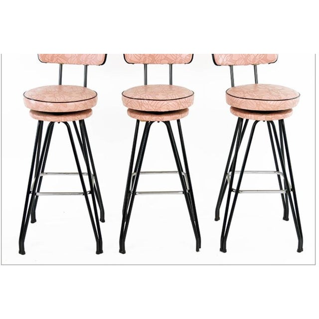 Set of three kitch mid-century bar stools with pink upholstery, black piping.