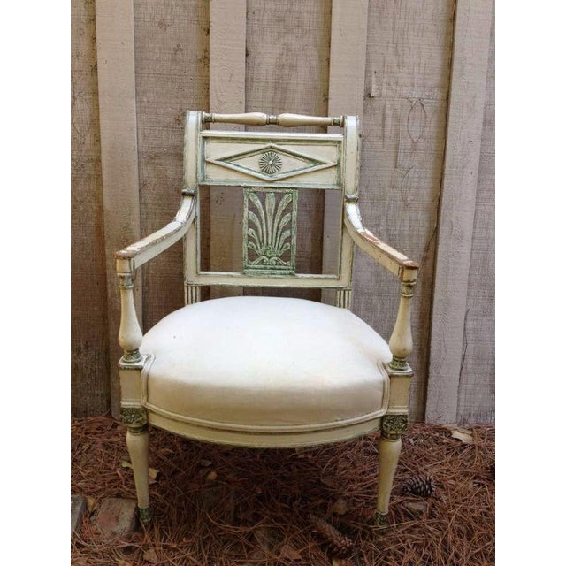 Pair of French Empire style fauteuils, cream paint with green accents, upholstered muslin seats.