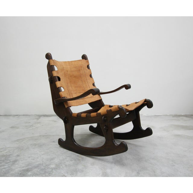 Primitive Style Leather and Wood Rocking Chair made in Ecuador by Angel Pazmino. Chair features hand tooled leather...