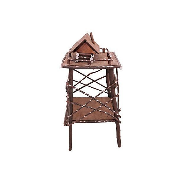 Circa 1940s handcrafted twig stand with silver paint decoration. A cabin is attached to top and the roof lifts off for...
