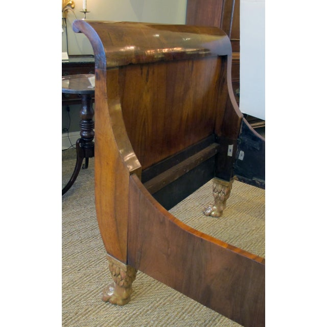 each with well-figured richly-patinated flared uprights joined by the original rails; raised on well-carved gilt-wood paw...