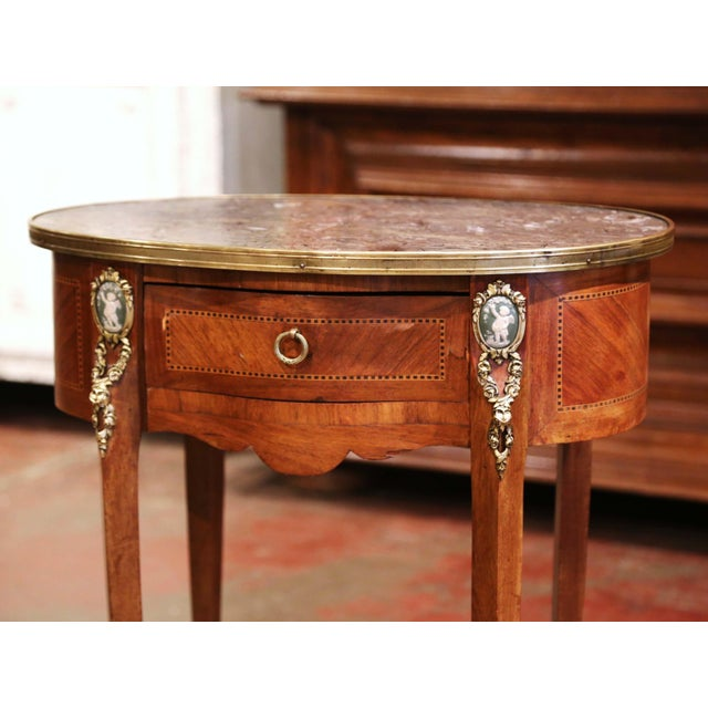 Crafted in France circa 1880, the elegant antique table stands on cabriole legs decorated with cherub porcelain plaque...