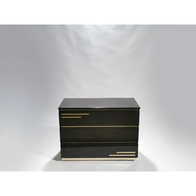 Crisp dark brown chocolate lacquer, paired with bright brass accents, feels creamy and luxe on this chest of drawers. It's...