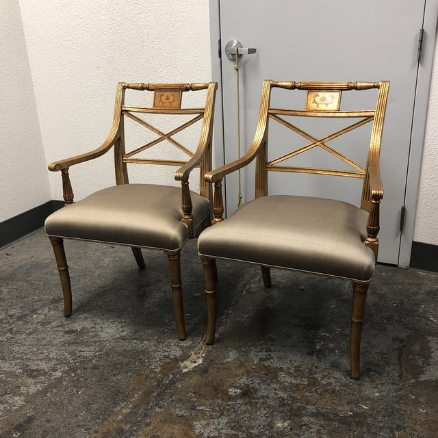 Pair of Louis XVI gold leaf gray silk upholstered armchairs. Noticeable conditions on silk upholstery. An X frame backrest...