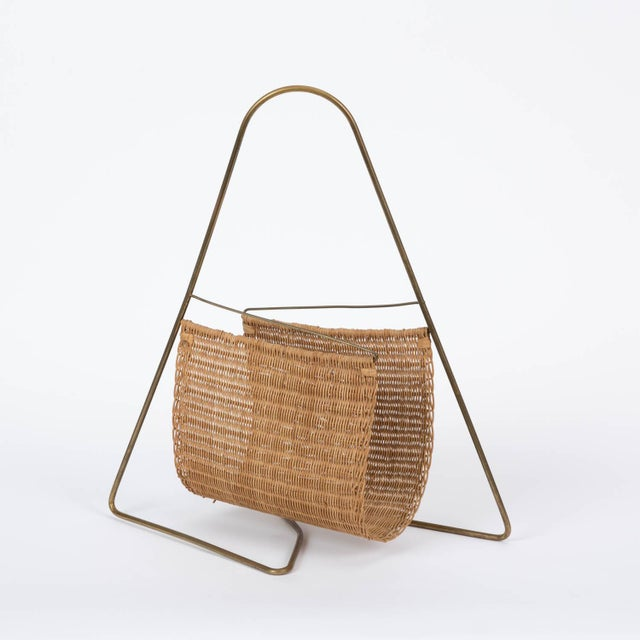 Brass and wicker magazine rack attributed to Austrian industrial designer Carl Auböck, c.1950. The rack has a bent tubular...
