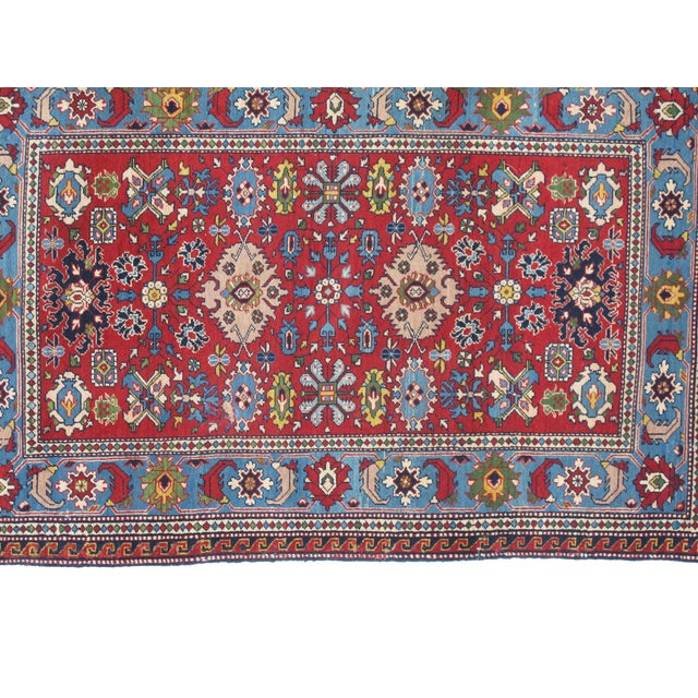 Wool pile hand woven antique red Russian rug in excellent condition.