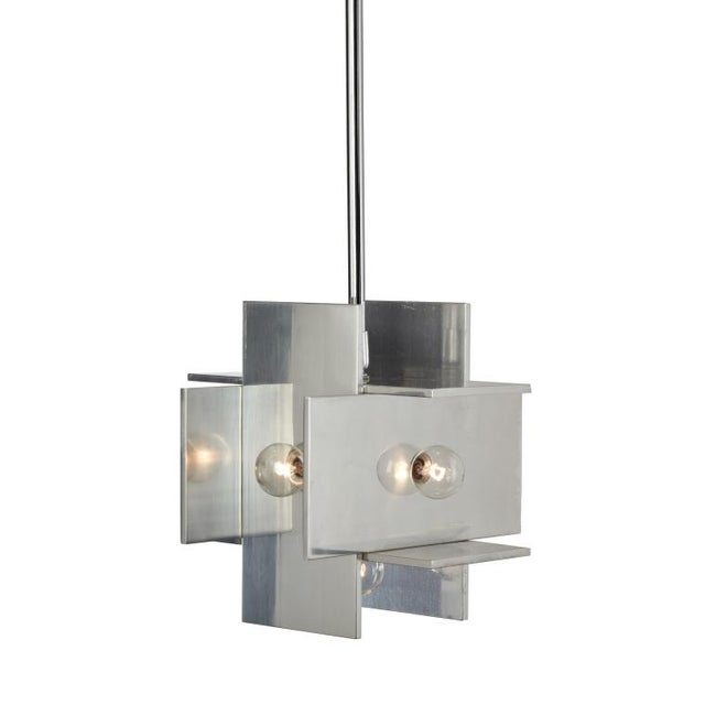 Two small pendant lights comprising thick aluminum sheets in perpendicular and parallel planes forming a perfect cube,...
