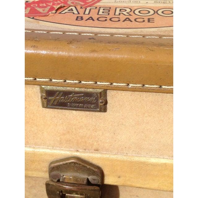 "A classic parchment-colored ""Vellum"" Mid-Century Hartman suitcase with original destination stickers. This piece of..."