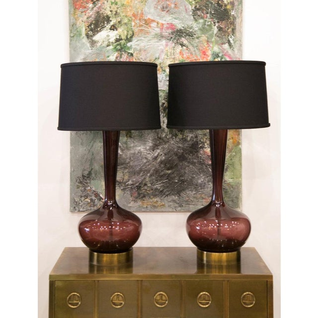 A gorgeous pair of handblown Murano glass lamps in a striking shade of plum with an elegant, shapely silhouette. These...