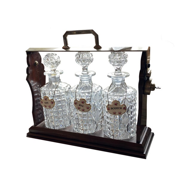 A tantalus containing three crystal decanters all locked in a wooden case and with rose painted labels for Gin, Rye and...