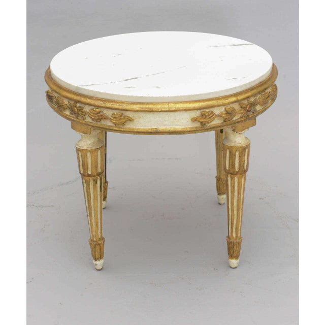 Round accent table, having white veined marble top inset in painted and parcel giltwood frame, its apron carved with...