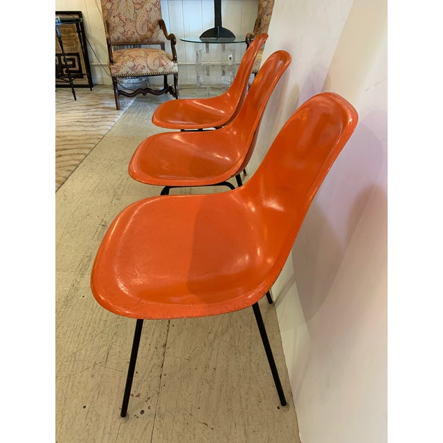 The classic DSX fiberglass chair designed by Charles Eames for Herman Miller having a bright orange color and black H...