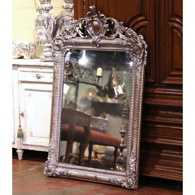 Crafted in France circa 1870, the heavily carved mirror is decorated with high relief scrolled decor including a center...